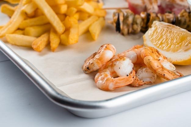 당근, 양상추 클로즈업과 함께 금속 접시에 구운 새우와 해산물 세트.