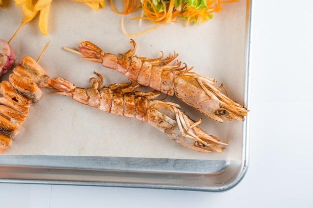 당근, 양상추 클로즈업과 함께 금속 접시에 큰 구운 새우와 해산물 세트.