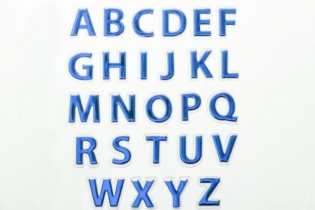 Набор блестящих синих глянцевых букв, изолированных на белом фоне. символ английского алфавита abc.