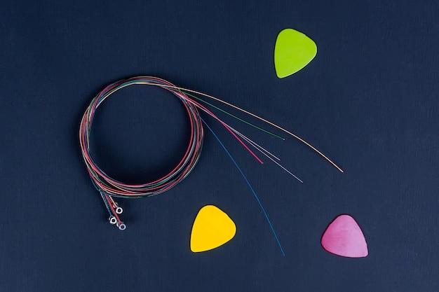 黒の背景にランダムに配置された6つのコイル状のアコースティックギターの弦のセット