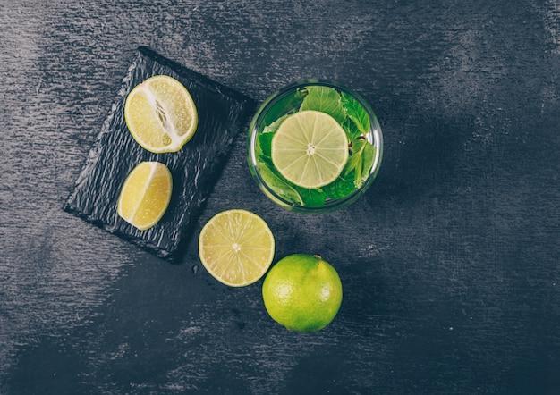 織り目加工の背景に黒の水のガラスのスライスとグリーンレモンのセット。上面図。