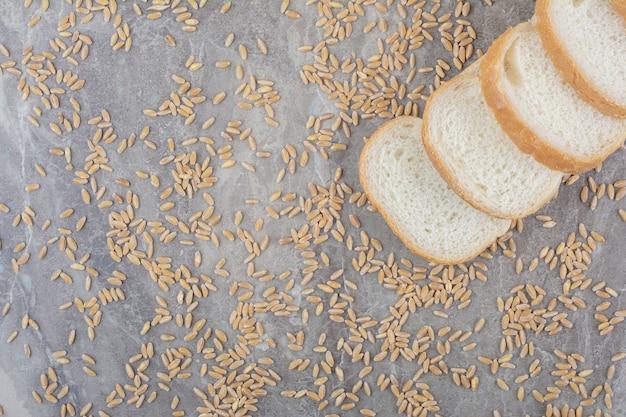 大理石の表面にオーツ麦の穀物とスライストーストパンのセット