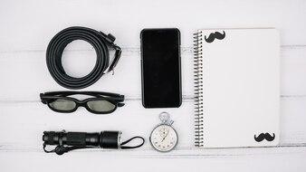 Набор смартфонов возле ноутбука и мужских аксессуаров