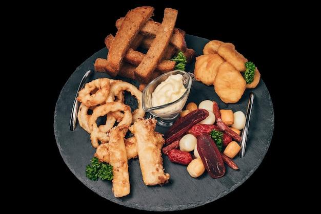 Набор закусок к пиву из крекеров, луковых колец, колбасы и сыра