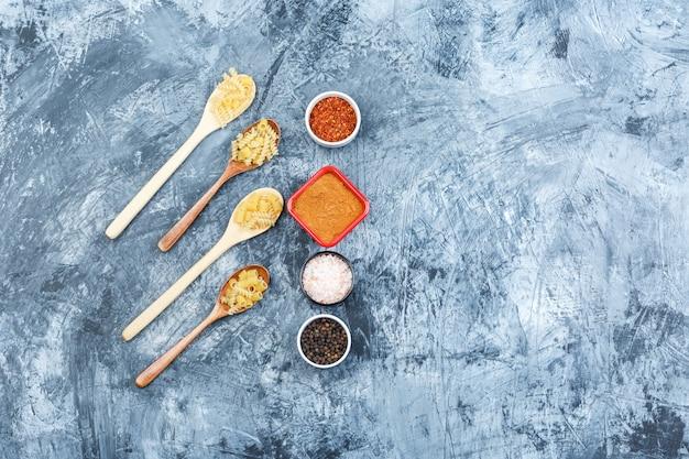 汚れた石膏の背景に木のスプーンでスパイスと各種パスタのセット。フラットレイ。