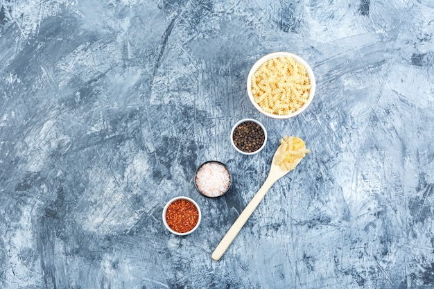 汚れた石膏の背景に白いボウルと木のスプーンでスパイスとフジッリパスタのセット。フラットレイ。