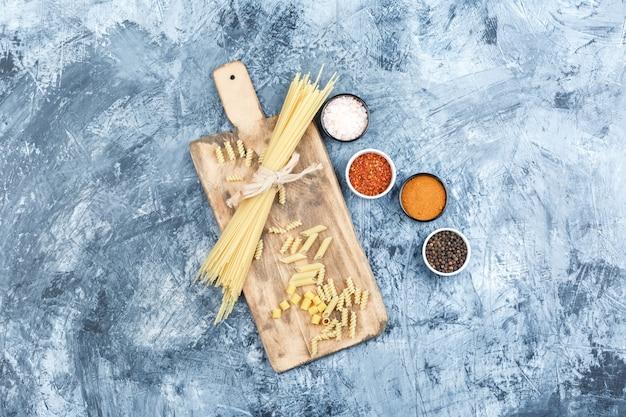 회색 석고와 커팅 보드 배경에 향신료와 스파게티의 집합입니다. 평면도.