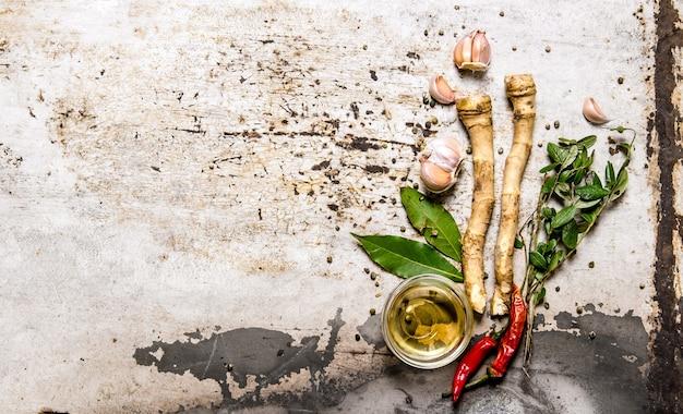 スパイスのセット-唐辛子、生姜、ニンニク、月桂樹の葉、オリーブオイル。