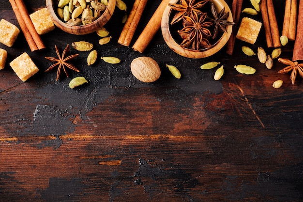 古い木製の背景にスターアニス、カルダモン、シナモン、ブラウンシュガーのスパイスのセットです。フラットレイ。