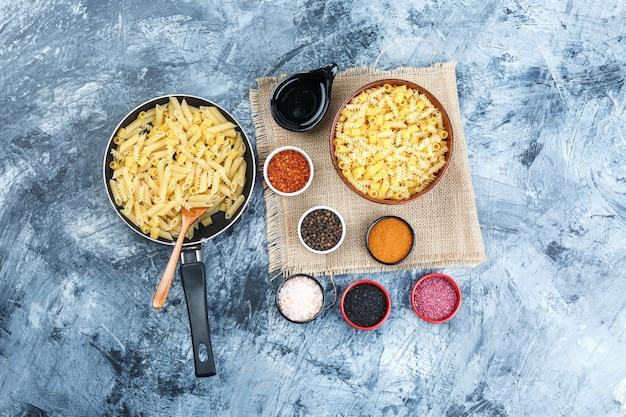 石膏と袋の背景の部分に鍋とボウルにスパイス、スクープ、木のスプーン、生パスタのセット。上面図。