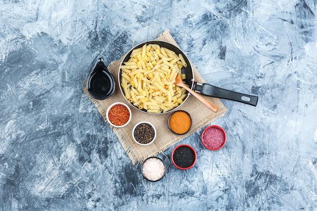 石膏と袋の背景の鍋にスパイス、スクープ、木のスプーン、生パスタのセット。上面図。