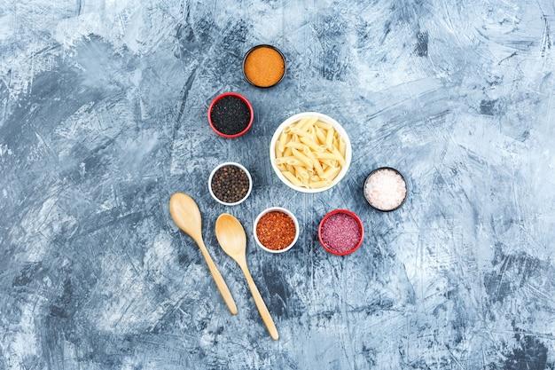 향신료, 나무 숟가락과 회색 석고 배경에 그릇에 펜 네 파스타의 집합입니다. 평면도.