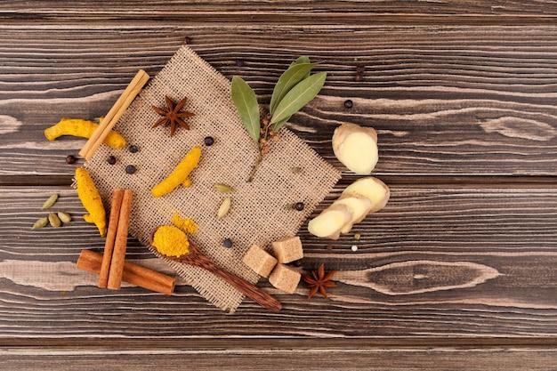 インドの飲み物を作るためのスパイシーなスパイスのセット:マサラティー、ゴールデンミルクなど。木製のテーブル。