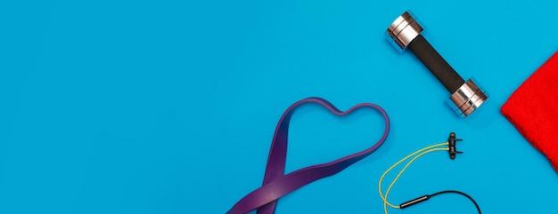 파란색 탁 트인 배경의 스포츠 액세서리 마사지 롤러, 스포츠 하네스, 헤드폰 세트