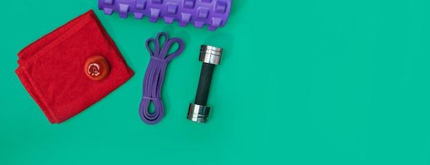 스포츠 액세서리 마사지 롤러, 스포츠 하네스, 녹색 탁 트인 배경에 헤드폰 세트