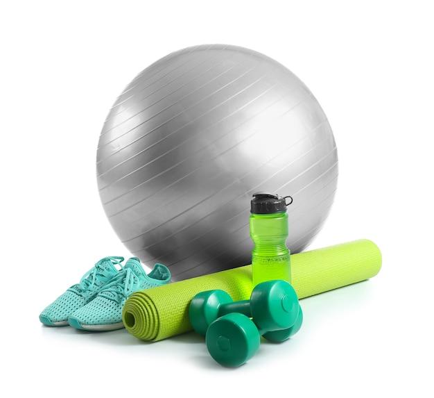 흰색 바탕에 피트니스 공, 신발, 물 한 병이 있는 스포츠 장비 세트