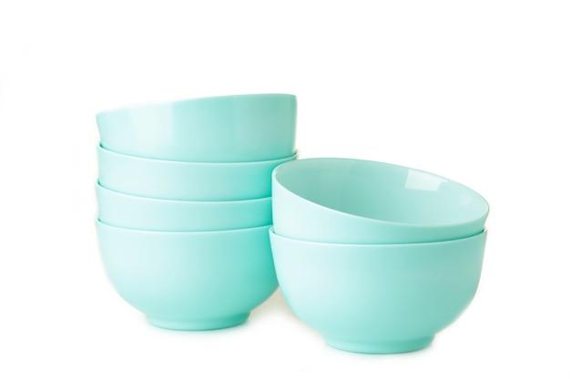 Набор сложенных мятных керамических тарелок для салата, изолированные на белом