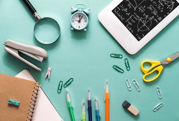 Набор канцелярских товаров на синем бумажном фоне. концепция готовности к экзамену и обратно в школу. бизнес-концепция. плоская планировка.