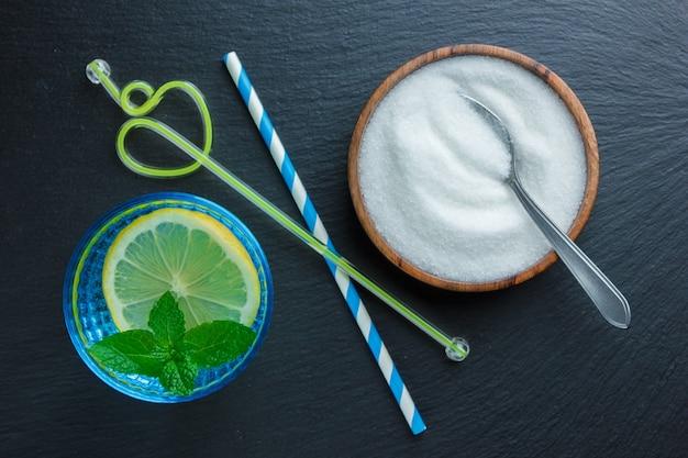 Набор соломинок, листьев и ложки с солью и ломтиком лимона в синей миске на темной каменной поверхности. вид сверху.