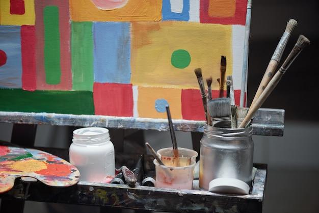 カラーパレット、ガッシュと絵筆の入った瓶、絵の入ったイーゼルなど、プロの絵画用のもののセット