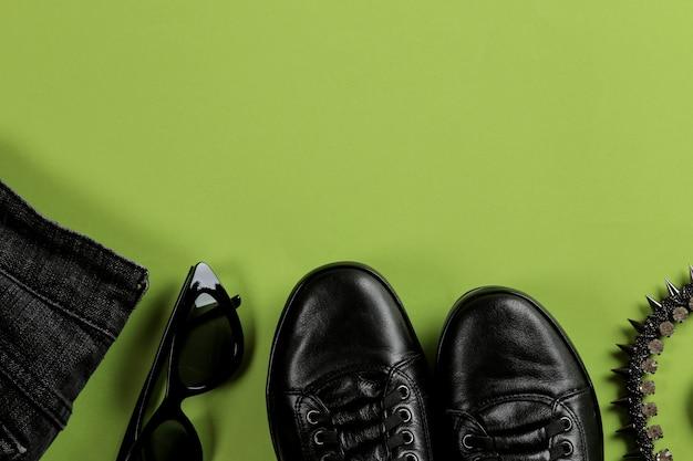 明るい緑の背景にスタイリッシュな黒の女性のアクセサリーのセットです。
