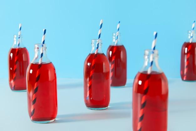 Набор летних коктейлей из клюквы со льдом в бутылках на синем фоне