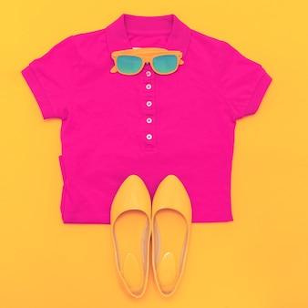 黄色の背景にサングラスシャツと靴のセット。明るい夏のスタイル
