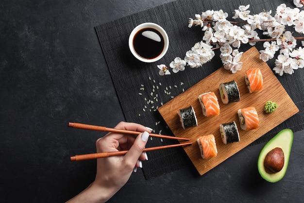 寿司とマキロール、スライスしたアボカド、箸と手と石のテーブルの上の白い花の枝のセット。上面図。
