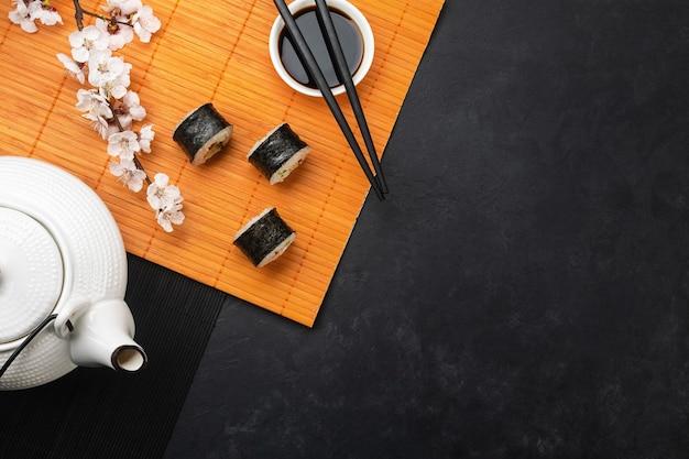 白い花の枝と石のテーブルの上のティーポットと寿司と巻き寿司のセット。上面図。