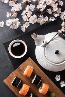 Набор суши и маки роллов с веткой белых цветов и чайник с надписью зеленый чай на каменном столе. вид сверху.
