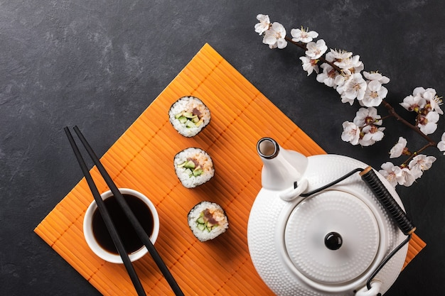 白い花の枝と石のテーブルに刻まれた緑茶とティーポットと寿司と巻き寿司のセット。上面図。