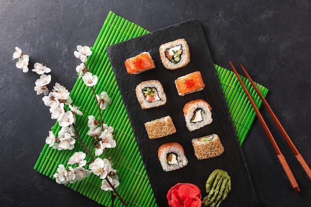 石のテーブルに白い花の枝と寿司と巻き寿司のセット。上面図。