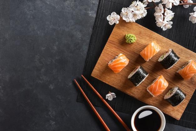 Набор суши и маки роллов с веткой белых цветов на каменном столе. вид сверху.