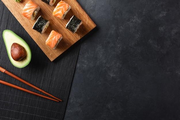 石のテーブルにスライスしたアボカドと寿司と巻き寿司のセット。上面図。