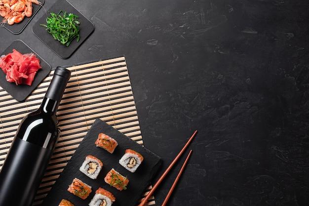 石のテーブルにワインのボトルと寿司と巻き寿司のセット。コピースペースのある上面図。