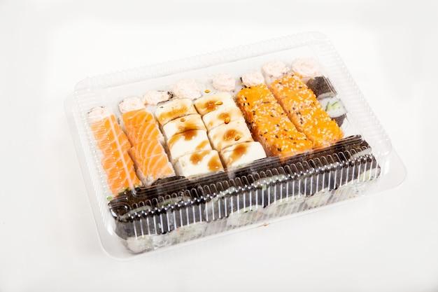 白い背景の上のプラスチック容器に寿司のセット。ロールパン配達。