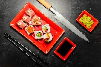Set of sushi, Japanese knife, chopsticks and on dark stone table. Wasabi, soy sauce. Sushi