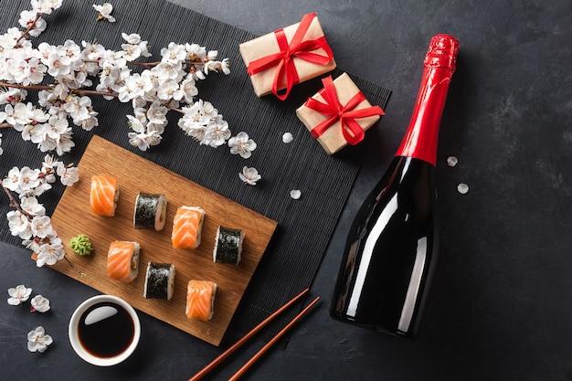 Набор суши, роллы маки, подарочные коробки и бутылка шампанского с веткой белых цветов на каменном столе. вид сверху.