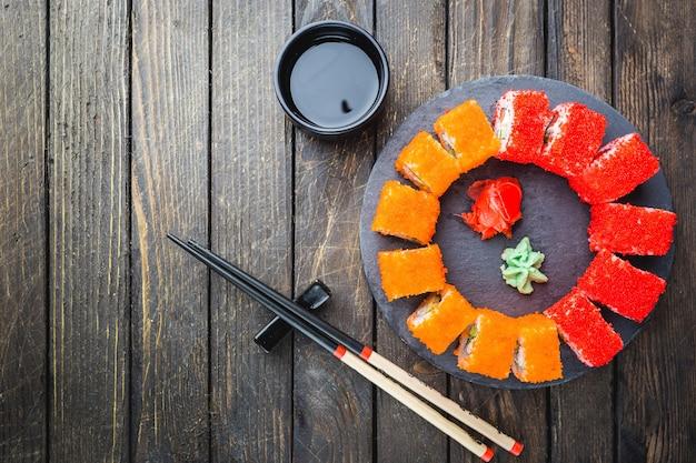 검은 나무 테이블 위에 돌 접시에 초밥 또는 마키 롤 세트