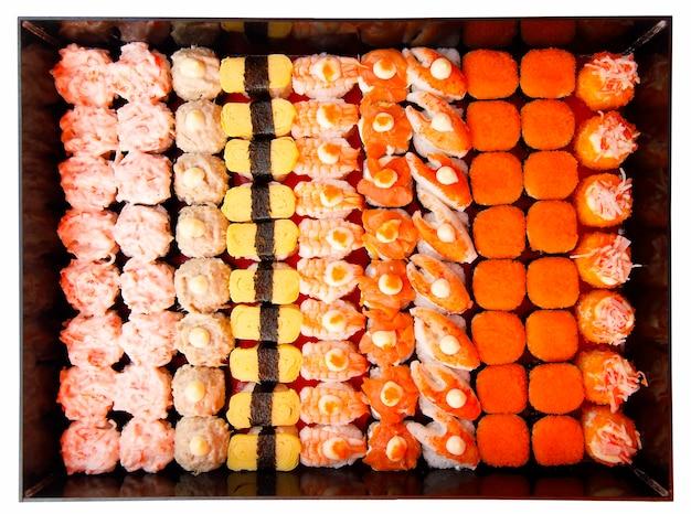 Набор суши, оригинальный стиль японской кухни, красочная и изысканная композиция в рядах. снято с вида сверху