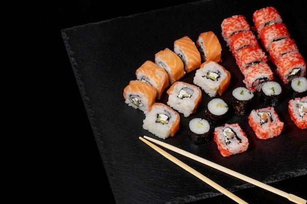 Набор суши-ролл на черном фоне сланца еда рыба филадельфия японский лосось вкусные суши рис огурец еда традиционные васаби свежие здоровые изысканные сырые блюда.