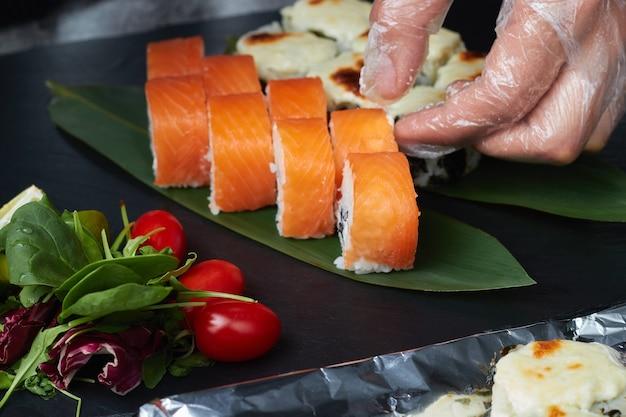 Набор суши-роллов лежит на бамбуковых листьях с лаймом, зеленью и красными помидорами, подается на черном каменном сланце.