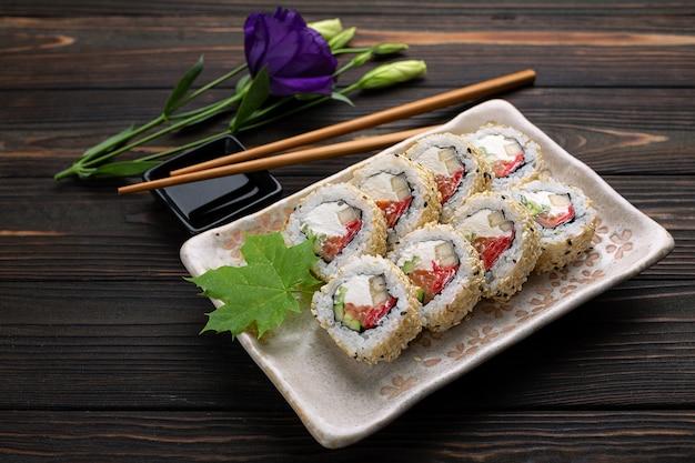 Набор суши-роллов со сливочным сыром, рисом и лососем на доске, декорированной имбирем на дереве