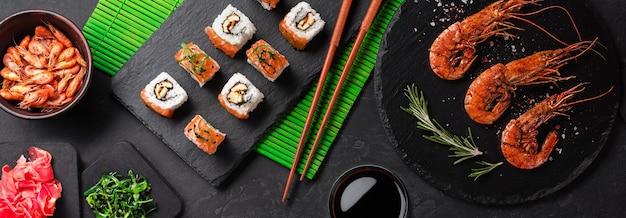 石のテーブルにワインのボトルと寿司、エビ、マキのセット。コピースペースのある上面図。