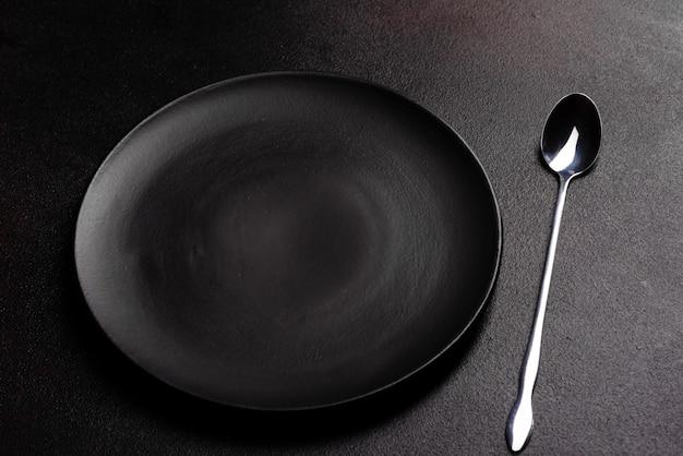 黒いコピースペースで食事の準備ができての食器のセット。金属製のナイフ、フォーク、スプーン、プレート
