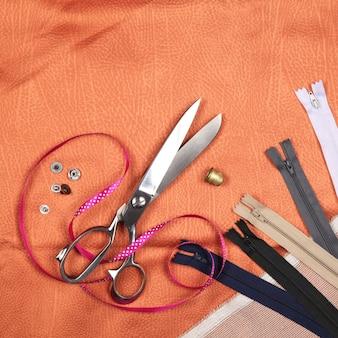 オレンジ色の生地に仕立てツールとアクセサリーのセット。上面図、フラットレイ。コピースペースあり