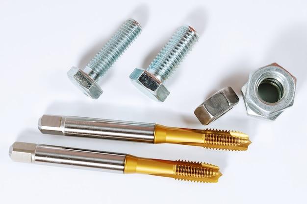 금속 나사 가공용 탭 세트. 볼트와 너트 흰색 배경에 고립입니다. 금속 가공용 도구.