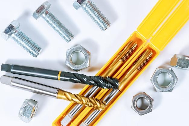 Набор метчиков для нарезания резьбы по металлу. болты и гайки, изолированные на белом фоне. инструмент для обработки металла.