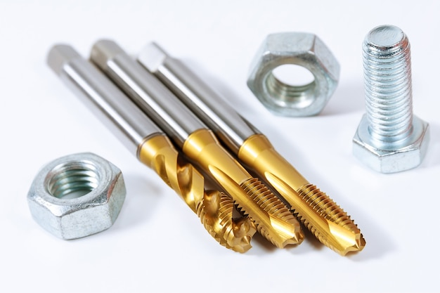 Набор метчиков для нарезания резьбы по металлу. болты и гайки, изолированные на белой поверхности. инструмент для обработки металла.