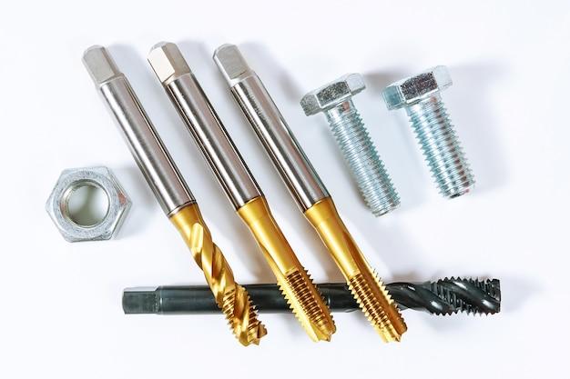 Набор метчиков для нарезания резьбы по металлу. болты и гайки на белом фоне. инструмент для обработки металла.